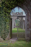 Archway with wooden gates at old abbey in Brecon Beacons in Wales. Norman archway with wooden gates in wall of ruined abbey in Brecon Beacons in Wales Stock Photos