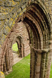 Archways of medieval abbey. Unusual angle of view showing an archway through an archway of Arbroath Abbey, Scotland. Geometry of architecture is emphasised Royalty Free Stock Photography