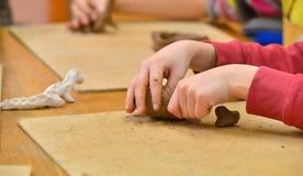 Arcilla en manos del niño Fotos de archivo libres de regalías
