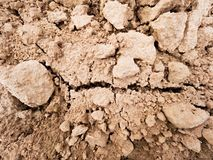 Arcilla polvorienta seca en el campo El campo arado vacío espera la siembra Día de aguas termales en el campo Imágenes de archivo libres de regalías