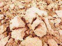 Arcilla polvorienta seca en el campo El campo arado vacío espera la siembra Día de aguas termales en el campo Imagen de archivo libre de regalías