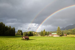 Arco-íris colorido durante a chuva nos cumes fotografia de stock royalty free