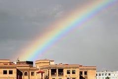 Arco-íris colorido largo multi-colorido brilhante após a tempestade no céu cinzento acima das casas de cidade ilustração do vetor