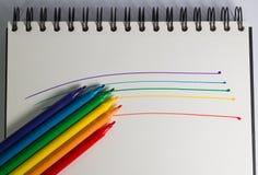 Arco-íris da pena de ponta de feltro em um caderno Imagem de Stock