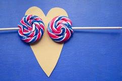 Arco-íris do redemoinho de Andy em volta de dois pirulitos no coração-dado forma Listras dos doces em uma vara no fundo azul Conc Imagem de Stock