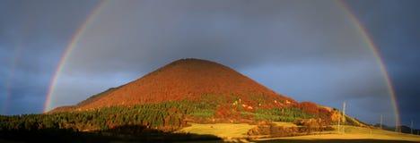 Arco-íris dobro bonito sobre o monte Imagem de Stock Royalty Free