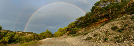 Arco-íris dobro no panorama da estrada Fotografia de Stock