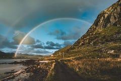 Arco-íris dobro sobre a aldeia piscatória pequena com céu azul e cloouds e montanhas nas ilhas de Lofoten, Noruega imagem de stock royalty free