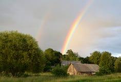 Arco-íris dobro sobre a floresta e as casas no campo fotografia de stock royalty free