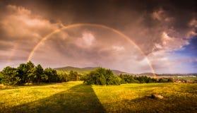 Arco-íris dobro sobre a paisagem no por do sol imagens de stock