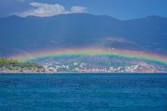 Arco-íris sobre a cidade pequena do litoral Fotos de Stock