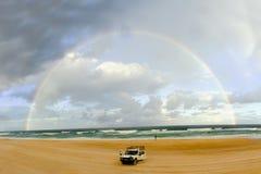 Arco-íris sobre o carro na praia Imagem de Stock Royalty Free
