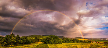 Arco-íris sobre a paisagem no por do sol foto de stock