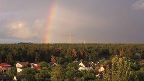 Arco-íris sobre a vila no lapso de tempo de Escócia Um grande arco-íris brilhante na perspectiva de um céu nebuloso no filme
