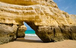 Arco amarillo de la piedra caliza en la playa arenosa del oro, ciudad de Portimao, Portugal imagen de archivo libre de regalías