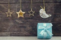 Arco azul del regalo con los ornamentos que cuelgan sobre de madera Imagenes de archivo