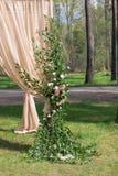 Arco beige di nozze decorato con i fiori Immagini Stock