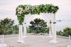 Arco blanco de la boda adornado con las flores, florales Fotografía de archivo