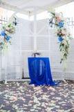 Arco blanco de la boda adornado con las flores y el paño Foto de archivo libre de regalías