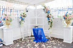 Arco blanco de la boda adornado con las flores y el paño Foto de archivo