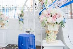 Arco blanco de la boda adornado con las flores y el paño Imagen de archivo libre de regalías