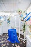 Arco blanco de la boda adornado con las flores y el paño Imagen de archivo