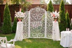 Arco blanco hermoso de la boda adornado con las flores Fotografía de archivo libre de regalías
