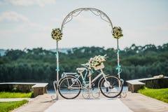 Arco blanco y azul adornado con el bycicle de las flores, casandose el registro al aire libre Fotografía de archivo