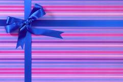 Arco blu del nastro del regalo di compleanno o di Natale sul fondo della carta da imballaggio della banda della caramella Immagini Stock Libere da Diritti