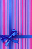 Arco blu del nastro del regalo sul fondo della carta da imballaggio della banda della caramella, verticale Immagini Stock