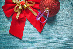 Arco brillante rosso della bagattella di Natale sul concep di feste del bordo di legno Immagini Stock Libere da Diritti