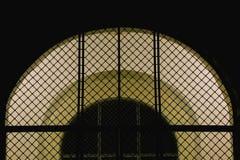 Arco cerrado de la malla del hierro con la puerta de entrada iluminada a la iglesia en la noche fotos de archivo libres de regalías