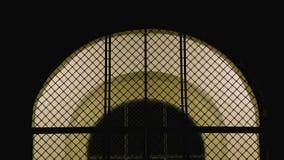 Arco cerrado de la malla del hierro con la puerta de entrada iluminada a la iglesia en la noche almacen de metraje de vídeo