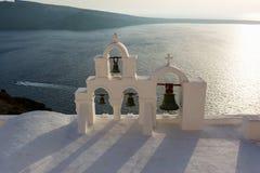 Arco com cruz e sinos da igreja branca grega tradicional na vila de Oia, ilha de Santorini, Grécia imagem de stock