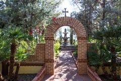 Arco con l'incrocio che conduce alla fontana nel giardino del monastero fotografia stock libera da diritti