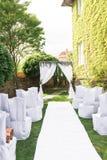 Arco de la boda adornado con el material blanco y mucho verdor La plataforma hermosa para una ceremonia de boda debajo del cielo  Fotografía de archivo