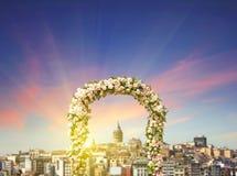 Arco de la boda adornado con las flores de rosas con la torre de Galata en la puesta del sol Fotografía de archivo libre de regalías