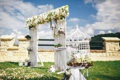 Arco de la boda adornado con las flores debajo del cielo azul con las nubes Imágenes de archivo libres de regalías