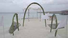 Arco de la boda adornado con las flores en la playa del océano contra el cielo y el agua en el centro turístico exótico metrajes