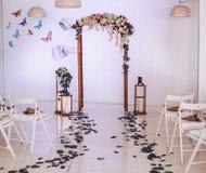 Arco de la boda adornado con las flores Palmatorias grandes con las velas en el cuarto con la decoración Ceremonia de boda Fotografía de archivo
