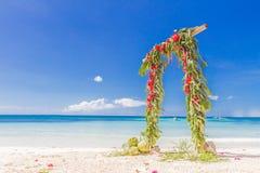 Arco de la boda adornado con las palmeras y las flores encendido Imagenes de archivo