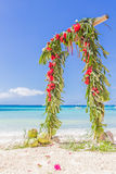 Arco de la boda adornado con las palmeras y las flores encendido Imágenes de archivo libres de regalías