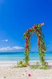 Arco de la boda adornado con las palmeras y las flores encendido Fotografía de archivo