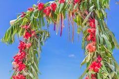 Arco de la boda adornado con las palmeras y las flores encendido Fotos de archivo