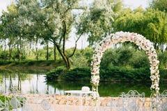 Arco de la boda adornado con las rosas de las flores, blancas y rosadas Con las sillas del vintage en un fondo de la charca en el Foto de archivo