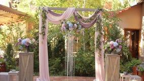 Arco de la boda con las flores frescas y los cristales en la ceremonia al aire libre almacen de metraje de vídeo