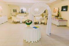 Arco de la boda en el interior brillante del restaurante adornado y servido para la celebración de la boda Imágenes de archivo libres de regalías