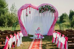 Arco de la boda para la ceremonia adornado con la tela y las flores blancas y rosadas Imagenes de archivo