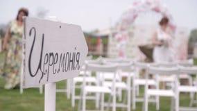 Arco de la ceremonia de boda, sillas para las huéspedes, accesorios de la boda y decoraciones metrajes