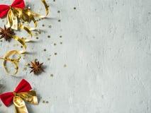 Arco de la Navidad y cinta rojos decorativos del oro en un copyspace concreto gris del fondo Foto de archivo libre de regalías